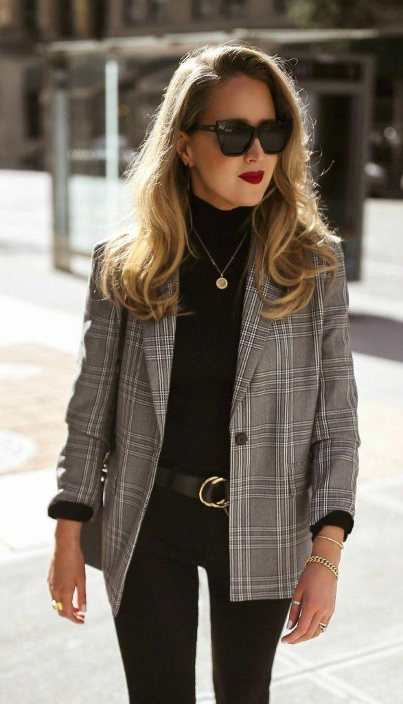 На девушке черная водолазка с высоким воротом, черные джинсы скинни, клетчатый серый пиджак прямого кроя. Образ дополнен аксессуарами: золотыми браслетами, тонкой золотой цепочкой с кулоном, чёрными очками.