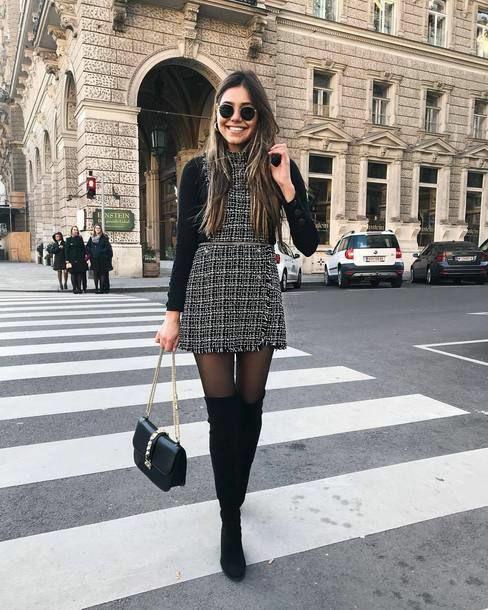 На девушке черная водолазка, твидовое платье без рукавов с прямой юбкой длины мини, полупрозрачные черные колготки, замшевые облегающие ботфорты выше колена, поясная черная сумка, черные круглые очки.
