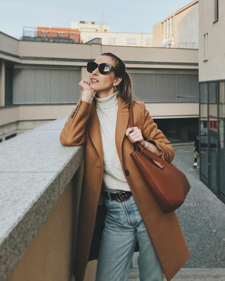На девушке светлая свободная водолазка с воротом, голубые прямые джинсы со средней талией, коричневое кашемировое пальто прямого кроя, коричневая кожаная сумка и черные очки.