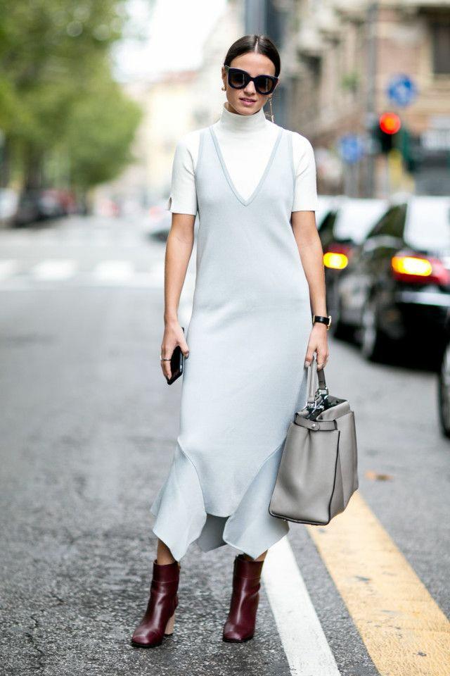На девушке белая водолазка с короткими рукавами и высоким воротом, светло-голубое прямое платье длины миди, с асимметричными вырезами и глубоким вырезом, кожаные темно-бордовые ботинки на толстом высоком каблуке, черные очки и серая сумка.