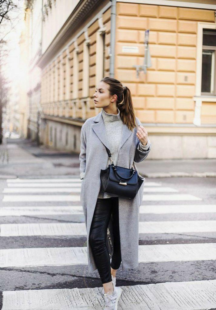 На девушке серая свободная водолазка с воротом, кожаные черные облегающие брюки, светлые кроссовки, светлое пальто прямого кроя длины макси, кожаная черная большая сумка через плечо.