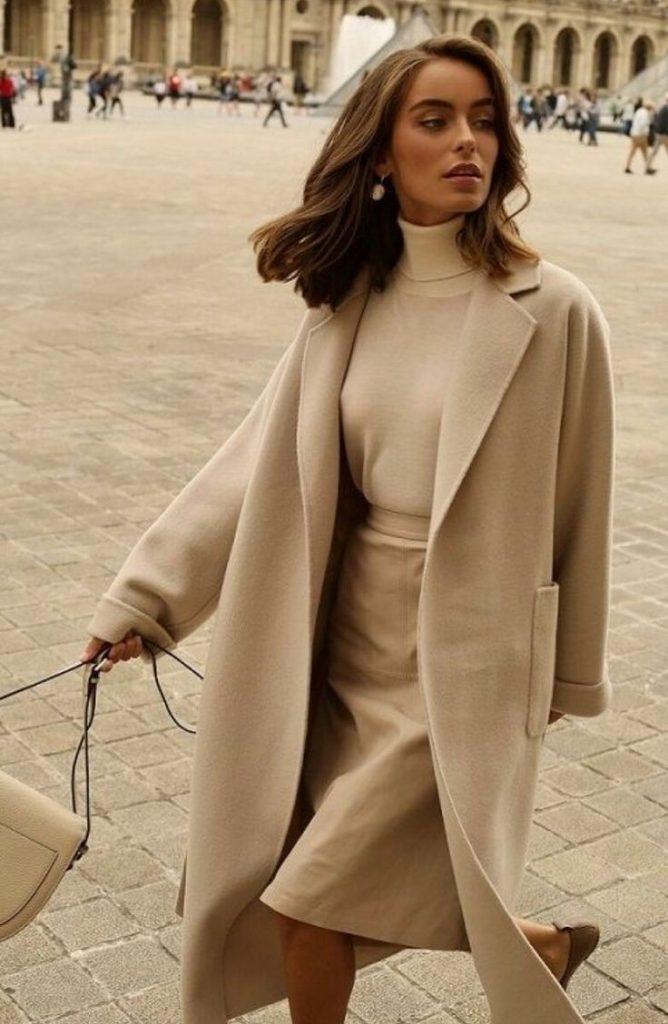 На девушке монохромный лук: бежевая свободная водолазка с высоким воротом, прямая юбка длиной до середины колена, кашемировое пальто прямого кроя, бежевая поясная сумка, туфли на плоском ходу.