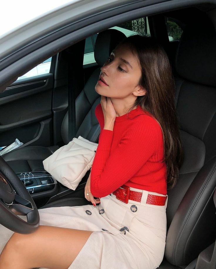 На девушке красная водолазка-лапша без ворота, белая прямая юбка миди с разрезом, декоративными пуговицами и красным кожаным ремнем.