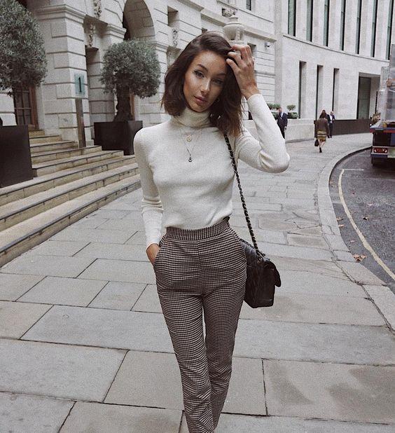 На девушке белая плотная водолазка с воротом, облегающие классические брюки с завышенной талией в мелкую клетку, кожаная черная поясная сумка и длинная тонкая цепочка.