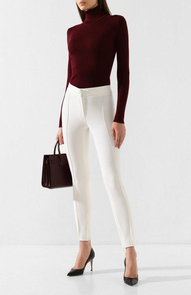 На девушке облегающая бордовая водолазка с воротом, белые облегающие брюки со стрелками и средней талией, кожаные лодочки с заостренным носом и на каблуке, тёмно-коричневая сумка.