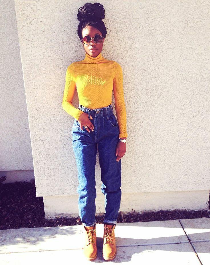 На девушке горчичная водолазка с воротом и узорами, синие джинсы бананы с высокой талией, горчичные ботинки на шнуровке, круглые солнцезащитные очки.