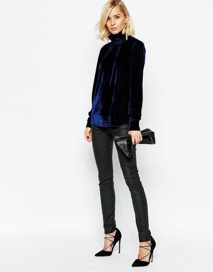 На девушке темно-синяя бархатная свободная водолазка с воротом, черные кожаные брюки скинни, черные лодочки на тонком каблуке и с заостренным носом, на шнуровке. Образ дополняют серьги, черный клатч.