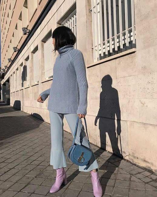 На девушке плотная свободная светло-голубая водолазка лапша с воротом, голубые прямые брюки с расклешенным низом, светло-розовые кожаные ботинки на низком толстом каблуке, синяя поясная сумка.