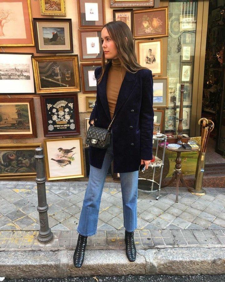 На девушке коричневая тонкая облегающая водолазка, синие джинсы-клеш, черные кожаные ботинки на шнуровке и с квадратным носом, темно-синий длинный вельветовый пиджак прямого кроя, поясная черная сумка.