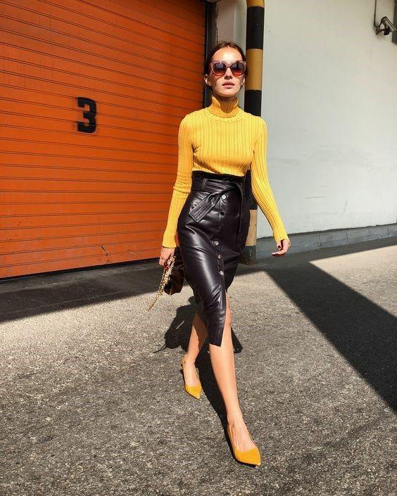 На девушке жёлтая облегающая водолазка-лапша с высоким воротом, кожаная черная юбка-карандаш длины миди, с разрезом спереди, присборенной талией и металлическими пуговицами, горчичные туфли с заостренным носом, коричневые квадратные очки.