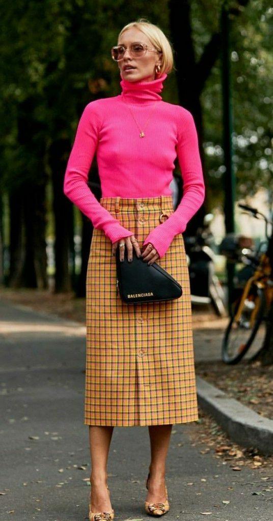 На девушке яркая розовая водолазка с объемным воротом, желтая прямая юбка длины миди в клетку, жёлтые туфли на каблуке и с заостренным носом, черная маленькая сумка Balenciaga, золотая тонкая цепочка, светло-розовые очки.