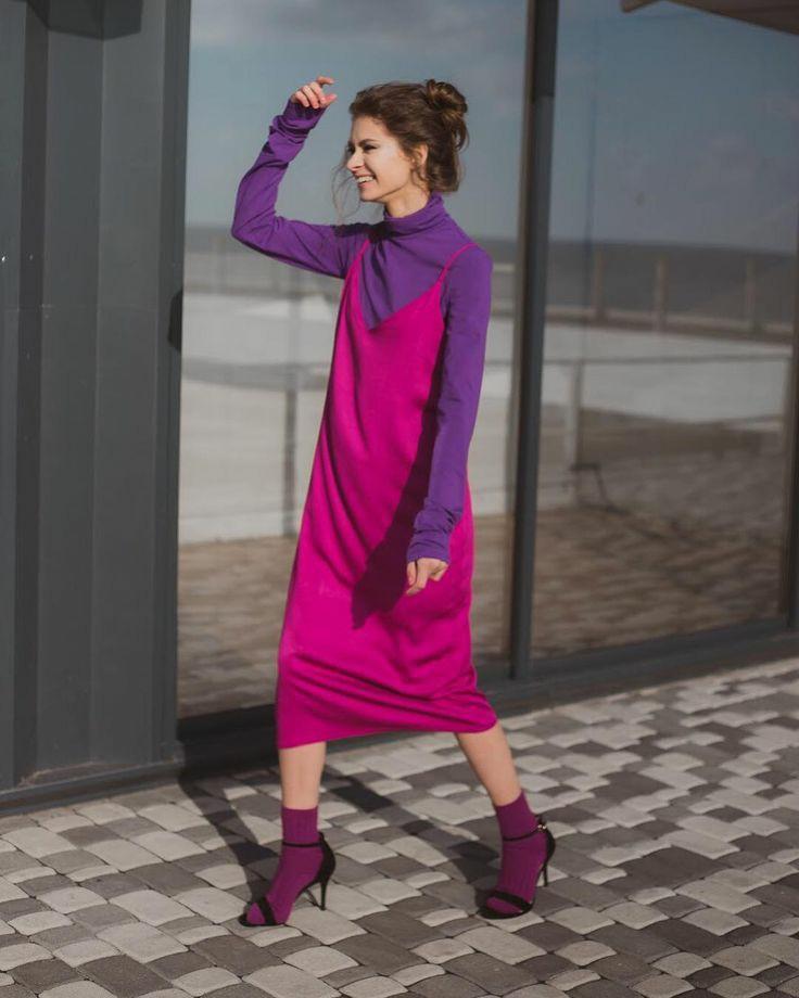 На девушке фиолетовая водолазка с воротом, шелковое яркое розовое платье свободного кроя длины миди, темно-фиолетовые носки, черные босоножки на тонком каблуке и с открытым носом.