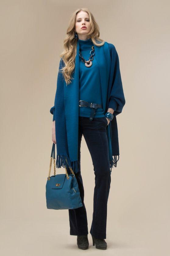 На девушке изумрудную свободная водолазка, вельветовые темно-синие облегающие брюки-клеш, замшевые ботинки на платформе и каблуке. Образ дополняют аксессуары: кожаный синий ремень, ожерелье, синяя сумка.
