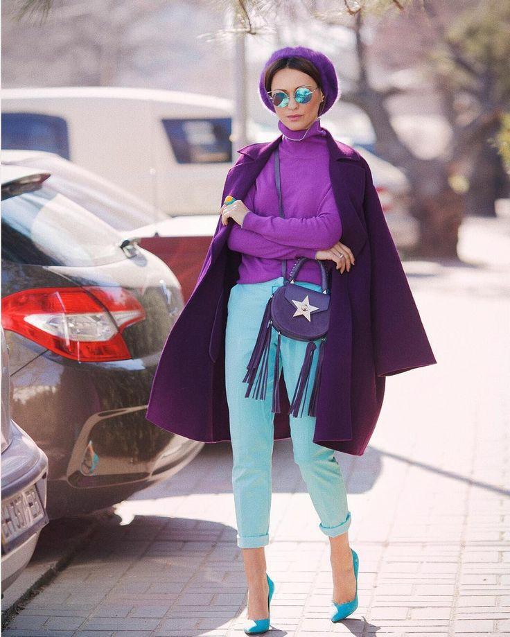 На девушке сиреневая водолазка с высоким воротом, мятные укороченные брюки со средней талией, голубые лодочки на каблуке и с заостренным носом, темно-фиолетовое пальто прямого кроя, фиолетовое кепи, поясная сумка с бахромой.