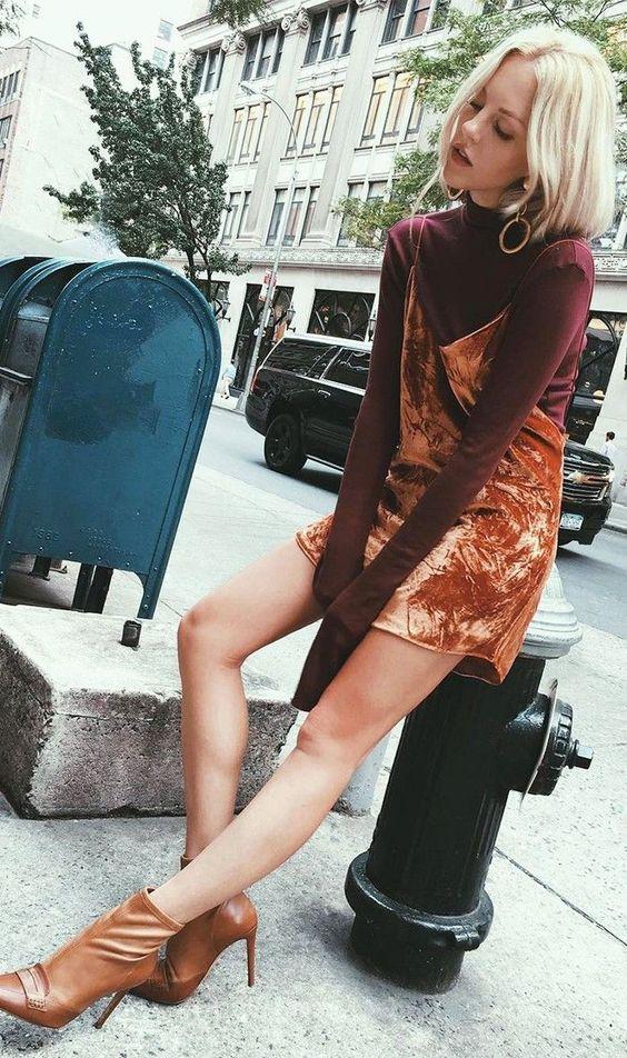 На девушке бордовая водолазка с коротким воротом, бархатное платье-мини на тонких бретелях оттенка манго, коричневые кожаные ботильоны на высоком тонком каблуке, золотые серьги.
