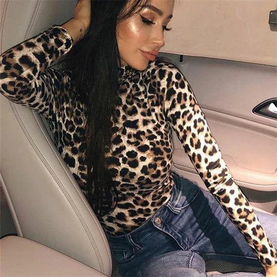 На девушке леопардовая облегающая водолазка и синие прямые джинсы со средней талией.