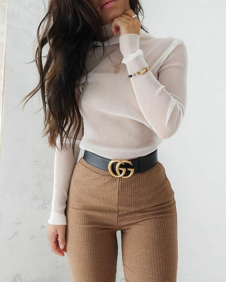 На девушке белая полупрозрачная свободная водолазка с горлом, вельветовые светло-коричневые брюки-скинни с завышенной талией, черный кожаный ремень, золотой браслет и тонкая золотая цепочка с кулоном.