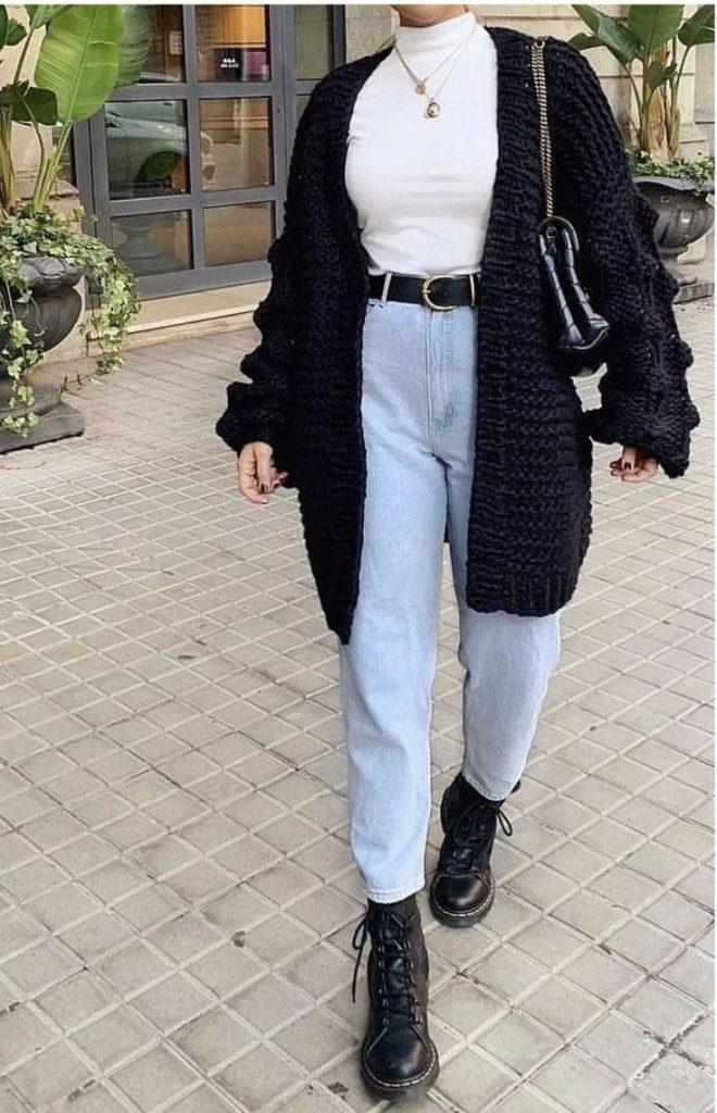 На девушке белая облегающая водолазка с воротом, светло-голубое джинсы моммы с завышенной талией, черные кожаные ботинки на платформе и шнуровке, вязаный черный кардиган, чёрный кожаный ремень, тонкие золотые цепочки с кулонами и поясная сумка.