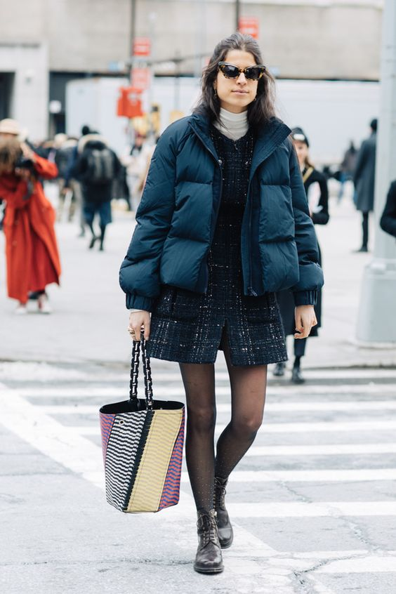 """На девушке белая водолазка с длинным воротом, твидовое платье-мини с пышной юбкой, полупрозрачные черные колготки, кожаные ботинки на шнуровке, объемный укороченный темно-синий пуховик, очки """"кошачий глаз""""."""