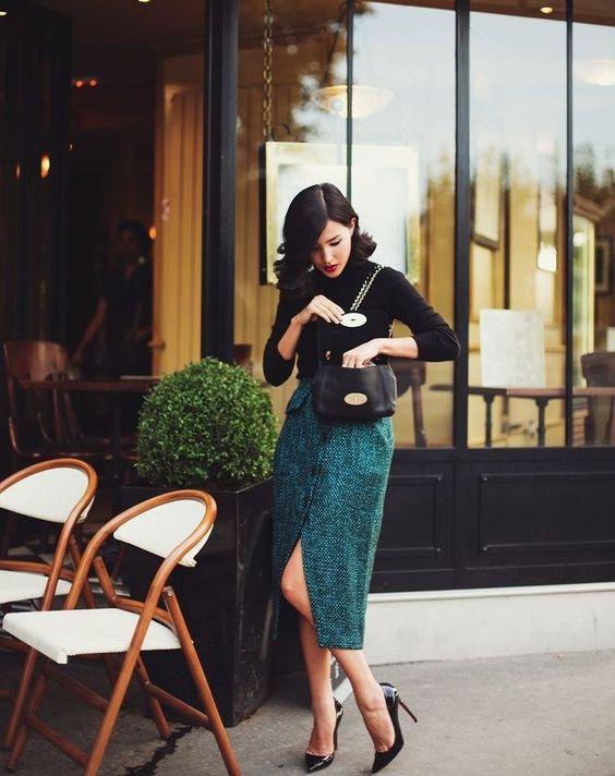 На девушке черная базовая водолазка, трикотажная прямая юбка-миди с разрезом спереди, карманами, пуговицами изумрудного цвета, лаковые черные лодочки с заостренным носом, черная сумка.