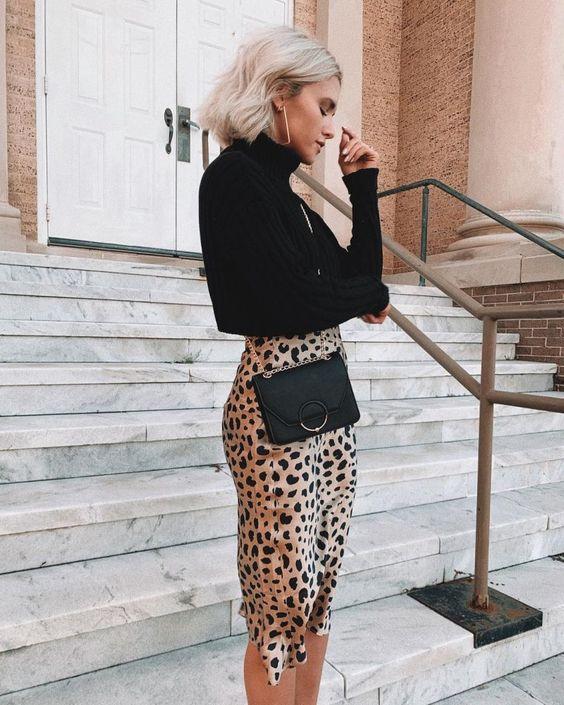 На девушке свободная черная водолазка с горлом, атласная юбка-карандаш ниже колена и с леопардовым принтом, поясная черная сумка-клатч.