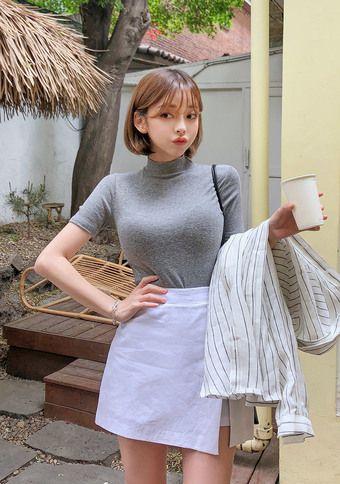На девушке серая тонкая водолазка с короткими рукавами и укороченным воротом, белая прямая юбка-мини с запахом, белая тонкая рубашка в горизонтальную полоску.