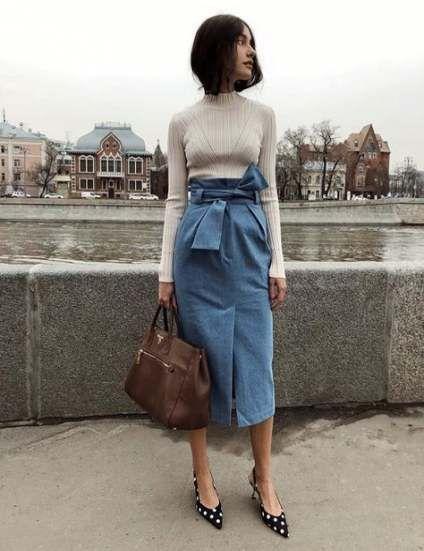 На девушке светло-бежевая водолазка в рубчик, джинсовая юбка-карандаш длины миди, с завышенной талией и поясом в виде банта, черные слингбэги в белый горошек, коричневая сумка-бочонок.