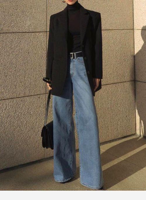 Черная облегающая водолазка с воротом в сочетании с темно-голубыми длинными джинсами-клеш с завышенной талией и черным кожаным ремнем, черным пиджаком прямого кроя, кожаной сумкой.