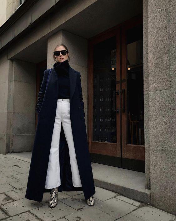 На девушке черная водолазка с объемным горлом, белые джинсы-клеш, ботинки с принтом крокодила на высоком толстом каблуке, темно-синее пальто оверсайз длины макси, черные квадратные очки.