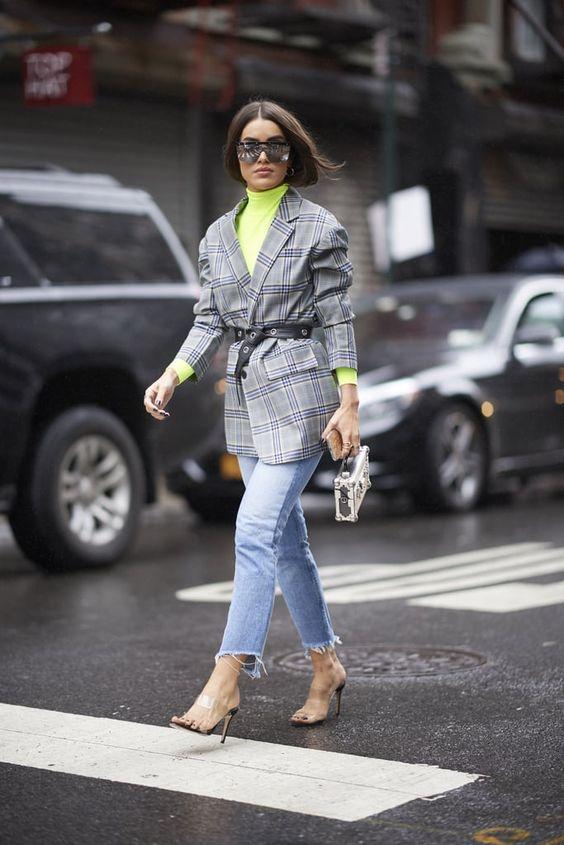 """На девушке яркая неоновая водолазка с воротом, серый клетчатый удлиненный пиджак с рукавами """"гармошкой"""", подчеркнутый кожаным черным ремнем, голубые прямые джинсы длины ⅞, босоножки на тонком высоком каблуке с прозрачными полосками, маленькая серая сумка и очки."""