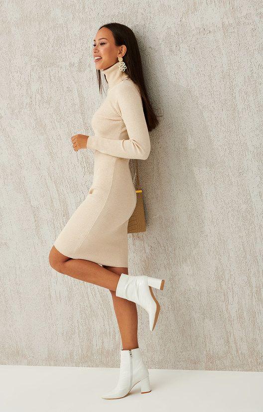 На девушке облегающее бежевое платье-водолазка немного выше колена, белые кожаные ботинки на толстом каблуке средней длины и с заостренным носом. Образ дополняют аксессуары: серьги, светло-коричневая сумка кроссбоди.