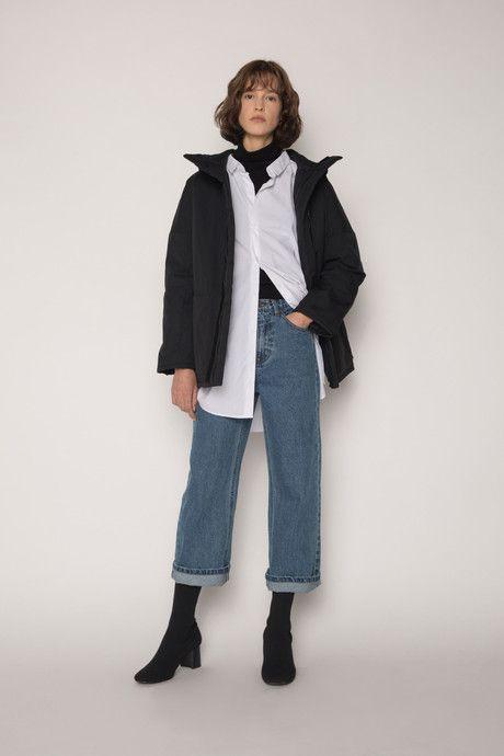 На девушке белая плотная рубашка оверсайз, надетая поверх черной водолазки с воротом, прямые синие джинсы со средней талией и отворотами, черные ботильоны-носки на толстом маленьком каблуке, черная куртка.