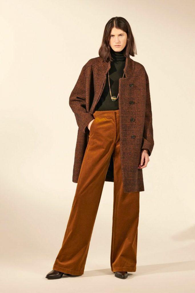 Черная водолазка с воротом в сочетании с коричневыми вельветовыми брюками-клеш, кожаными ботинками на каблуке с заостренным носом, клетчатым шерстяным пальто, длинной золотой цепочкой с кулоном.