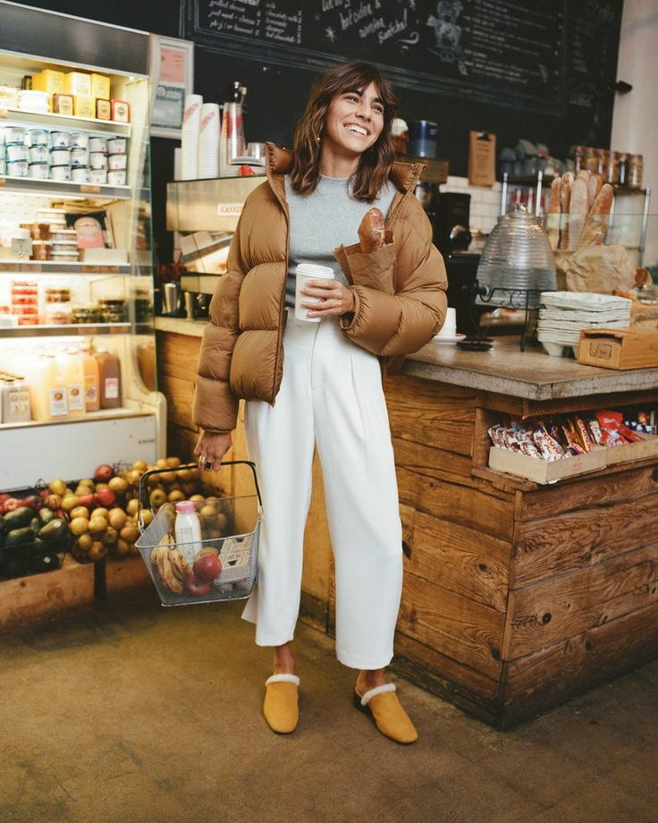 На девушке серая водолазка без ворота, белые прямые трикотажные брюки, желтые мюли с белым мехом, дутая укороченная светло-коричневая куртка оверсайз.