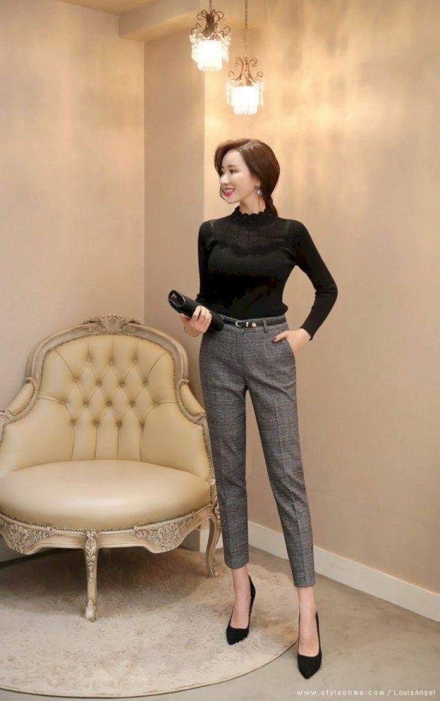 На девушке черная водолазка с кружевной вставкой на груди и ажурным воротом, шерстяные серые классические брюки с черным кожаным ремнем, черные лодочки с заостренным носом, черный клатч.