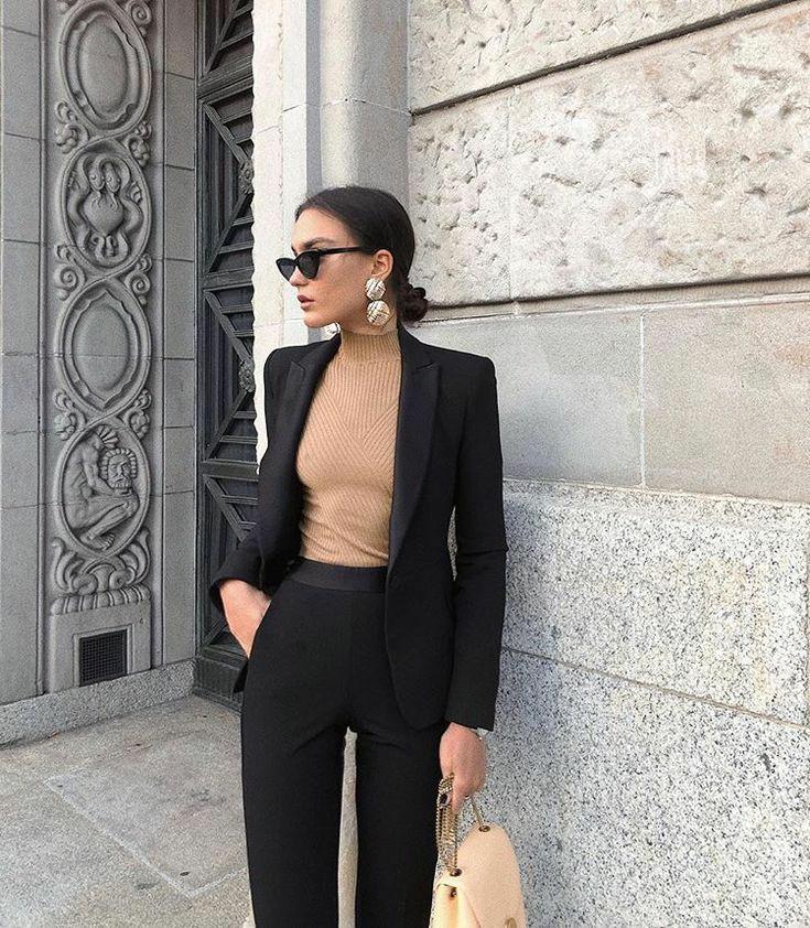 """Бежевая облегающая водолазка в рубчик в сочетании с черным прямым пиджаком и классическими облегающими черными брюками. Образ дополняют аксессуары: черные очки """"кошачий глаз"""", нежно-розовая сумка, круглые массивные серьги."""