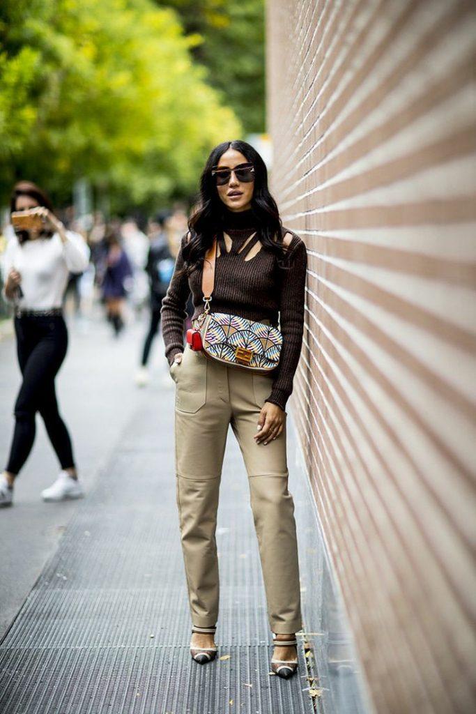 Тёмно-коричневая водолазка с горлом и вырезами на груди в сочетании со светлыми прямыми кожаными штанами, туфлями на каблуке, поясной сумкой почтальона, очками.