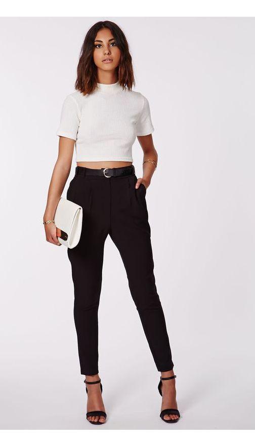 Девушка надела белую укороченную водолазку-лапшу с короткими рукавами, черные брюки-галифе, черные босоножки Анкл Стрэп, белый клатч.