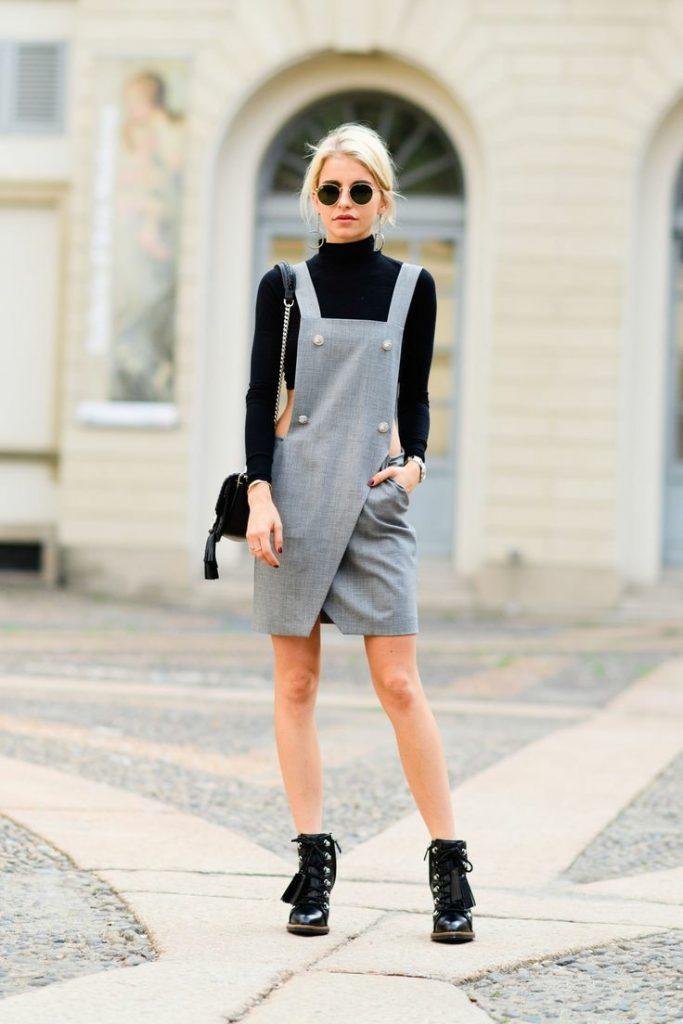 На девушке черная базовая водолазка, серый сарафан на запах с белыми пуговицами и квадратным вырезом, кожаные черные ботинки на шнуровке. Образ дополняют аксессуары: круглые черные очки, поясная сумка.