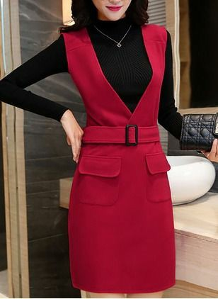 На девушке черная базовая водолазка, серебряная тонкая цепочка, красный облегающий сарафан с глубоким декольте, ремнём и декоративными карманами.