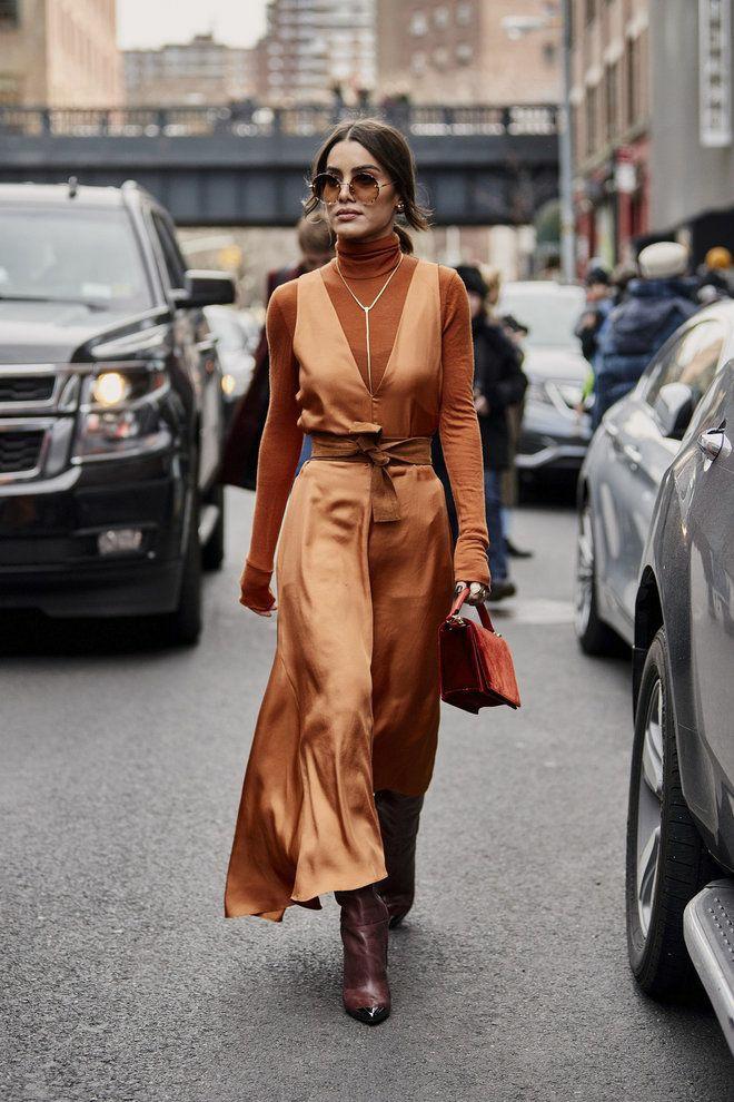 На девушке коричневая водолазка с высоким воротом, шелковое платье-макси светло-коричневого цвета с глубоким декольте и коричневым поясом, кожаные сапоги с заостренным носом, светло-коричневые очки, длинная цепочка и замшевая бордовая сумка.