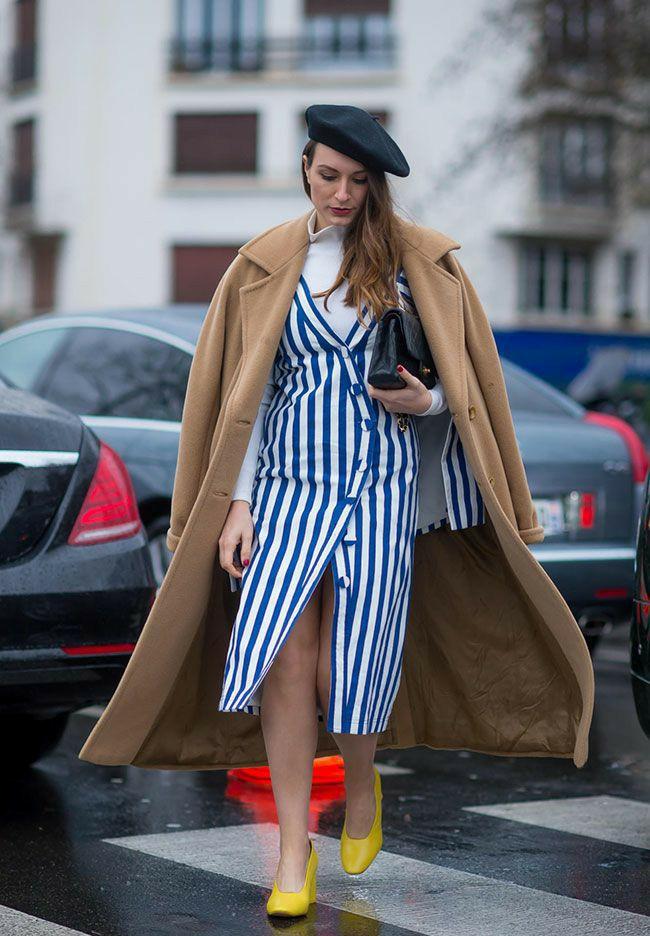 На девушке белая водолазка с воротом, белое платье с горизонтальными синими полосами длины миди, с разрезом спереди, V-образным воротом, пуговицами, желтые туфли на каблуке, бежевое кашемировое пальто длины макси, черная кожаная сумка.