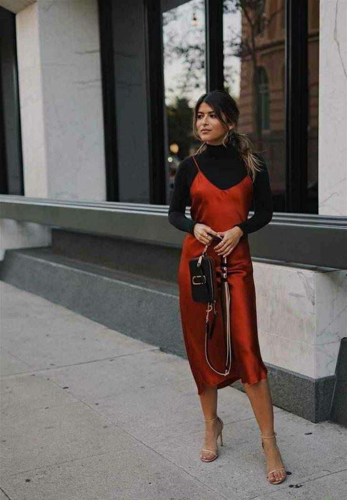 Черная облегающая водолазка в сочетании с шелковыми красным платьем ниже колена и на тонких бретелях, босоножками на тонком каблуке и ремешках, поясной сумкой-клатчем.