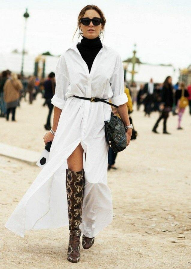 На девушке черная водолазка с длинным воротом, белое платье-рубашка длины макси с разрезом спереди и тонким черным ремнем, свободные ботфорты выше колена с анималистическим принтом, черные очки, часы и черная сумка.