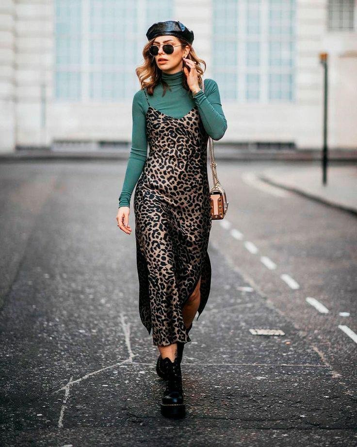 Зеленая облегающая водолазка с воротом в сочетании с атласным леопардовым платьем длины макси на тонких бретелях, черными кожаными ботинками на шнуровке, черными круглыми очками, кожаным кепи и поясной сумкой-футляр.