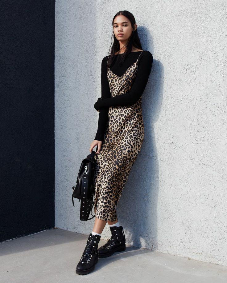 """На девушке черная водолазка с вырезом """"лодочка"""", шелковое леопардовое прямое платье длины миди на тонких бретелях, белые высокие носки, кожаные ботинки на шнуровке с металлическими вставками, большая кожаная сумка."""