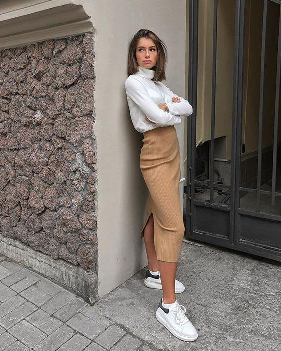 На девушке белая свободная водолазка с объемным высоким воротом, светло-коричневая трикотажная юбка-карандаш длины миди, с разрезом сзади, белые кроссовки.