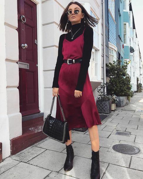 На девушке черная базовая водолазка с воротом, бордовое атласное платье на бретелях длиной до колена, подчеркнутое кожаным черным ремнем, кожаные черные ботильоны-носки . Образ дополнен аксессуарами : черные круглые очки, тонкая серебряная цепочка, кожаная сумка с металлической цепочкой.