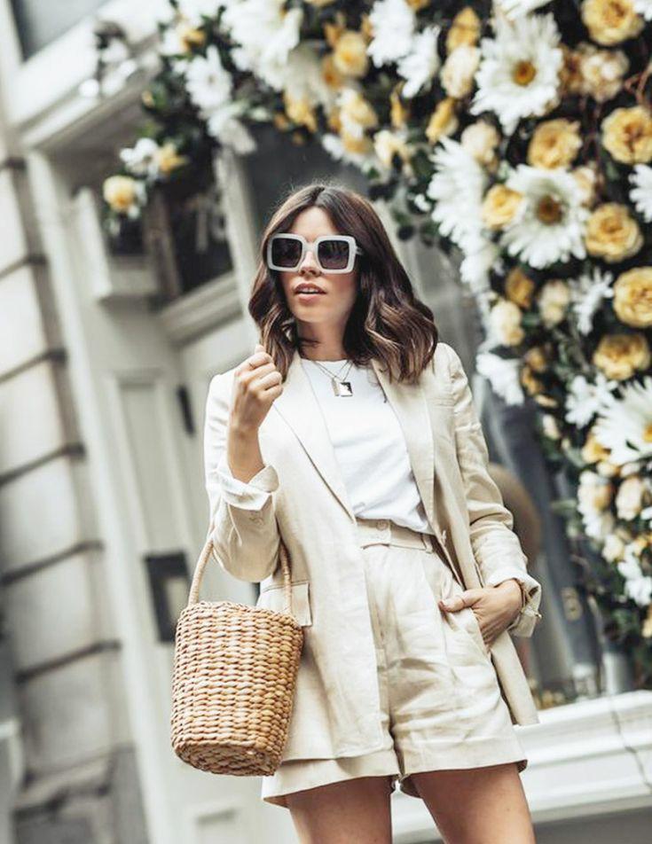 На девушке бежевый костюм из натуральных тканей: короткие шорты свободного кроя с завышенной талией, пиджак прямого кроя с карманами. Образ дополнен веревочной квадратной сумкой, квадратными очками с белой оправой, серебряной цепочкой с кулоном.