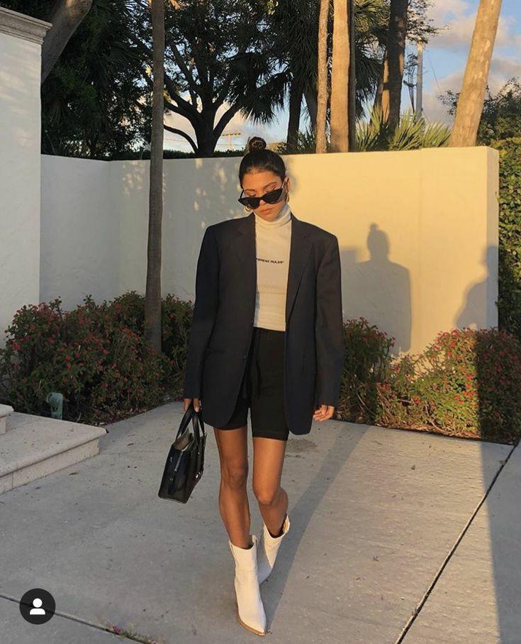 Бежевая облегающая водолазка с воротом и надписью в сочетании с облегающими шортами и черным пиджаком оверсайз, белыми кожаными сапогами с заостренным носом, черной сумкой и очками.